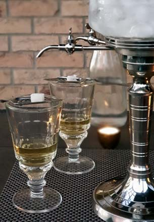 Absinthe Fountain, Glasses with Absinthe, Slotted Spoons and Sugar