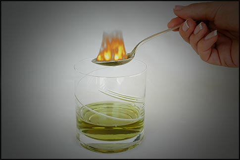 A spoon above the absinthe drink in a glass, with sugar on fire.
