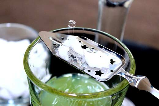 Absinthe drink in a glass with slotted absinthe spoon and sugar